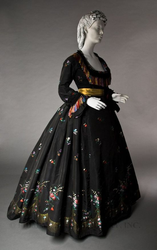 (1/3) 1866 black silk faille two-piece dress. Though it appears extremely formal and elegant to our contemporary eyes, it would have been worn to a dinner or reception, rather than the most formal of evening balls.  The black ground creates a luxurious contrast to the multicolored floral sprays, which feature poppies, roses, and bleeding hearts among other flowers.