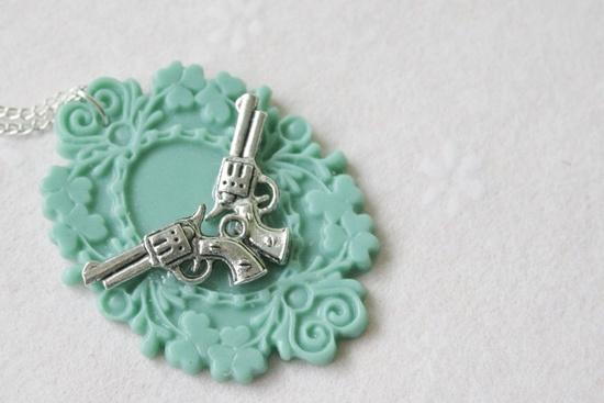 Gun Necklace / Handgun Necklace / Silver-plated Handmade Gun Coat-of-arms Charm Necklace. $16.95, via Etsy.
