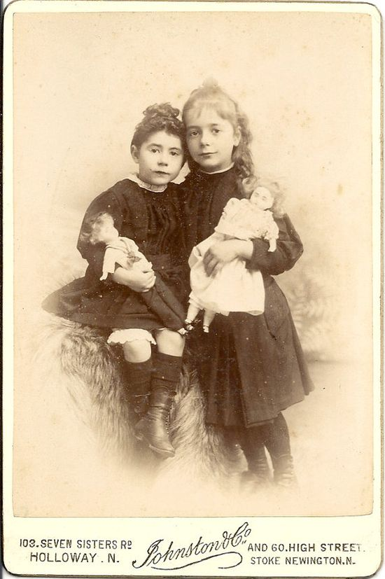 cabinet photo of sisters with their dolls. Circa 1890 - 1900.