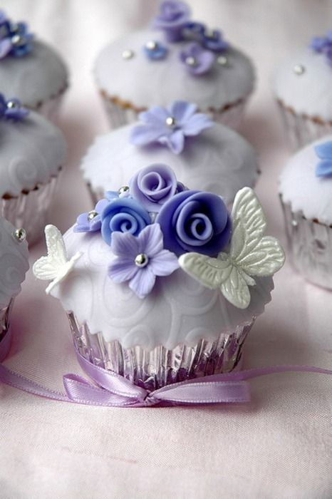 Resplendently beautiful flower and butterfly topped wedding cupcakes. #food #wedding #cake #cupcakes #butterfly #flowers #purple
