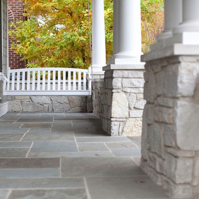 beautiful covered porch with swing.  Love the stone bases on the columns and the stone tile floor