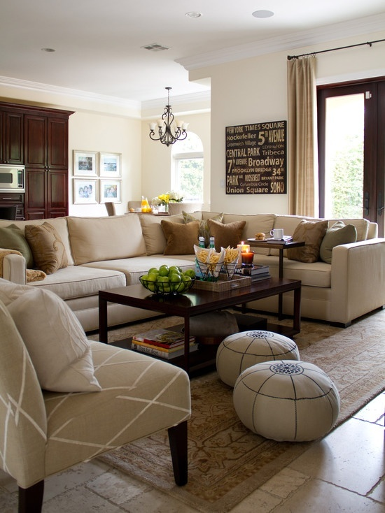 Family room with casual feel and earth tones. Beige sofas and chairs with wooden coffee table and cabinets. Designed and styled by Shirry Dolgin.