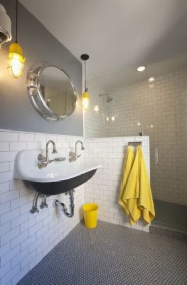 the boys bathroom uses subway tiles on the walls and  penny tiles on the floor, and is accented with yellow accessories.