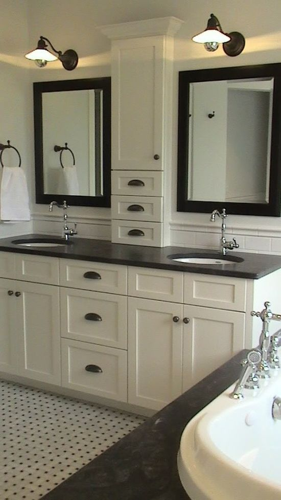 Black and white bathroom with storage between the sinks