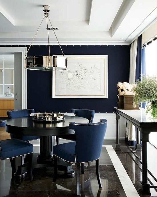 Tailored Elegance designed by Pablo Paniagua, crisp, tailored, and decidedly masculine. The color palette of navy, white, and rich-colored woods adds to the polished effect. I love simple nickel pendant and the studded trim on the walls.
