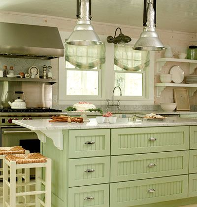Soft Sea Green: The green color of the cabinets absorbs light in this open, white kitchen – white on white would have been too much.