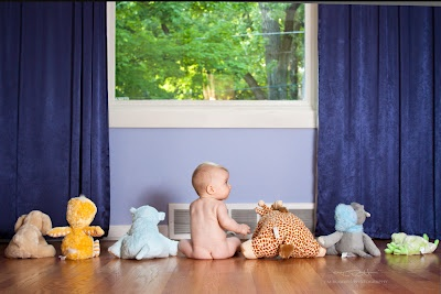 A little boy having fun with his stuffed animals.  Baby Photography