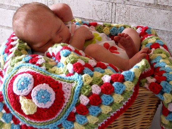 Blanket with crocheted applique.