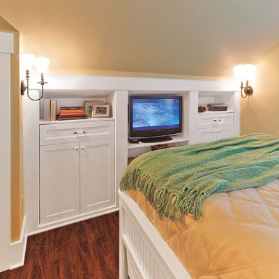 Built-in flat-panel cabinets and open shelves tuck media equipment under the sloped ceiling.