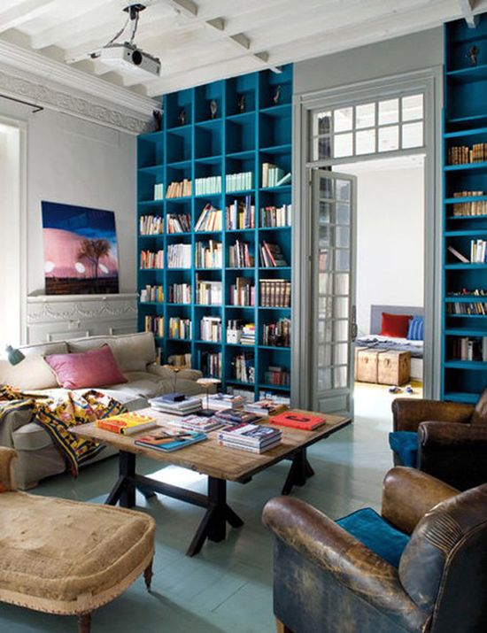 Incorporate a library to house all your books right in the family room. And bright blue shelves at that! This room is so comfortable. I adore all of the eclectic touches (the blue velvet cushion on the brown leather arm chairs!). A family could gather in here for game nights and to watch movies.Love the ceiling, door & transom windows. Cool space.