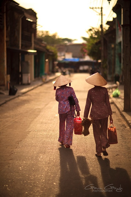 Two women in traditional, conical non hats walking along a street near the market in Hoi An, Vietnam