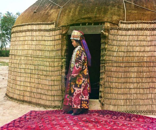 In this portrait, Prokudin-Gorksii captures the traditional dress, jewelry, and hairstyle of an Uzbek woman standing on a richly decorated carpet at the entrance to a yurt, a portable tent used for housing by the nomadic peoples of Central Asia.