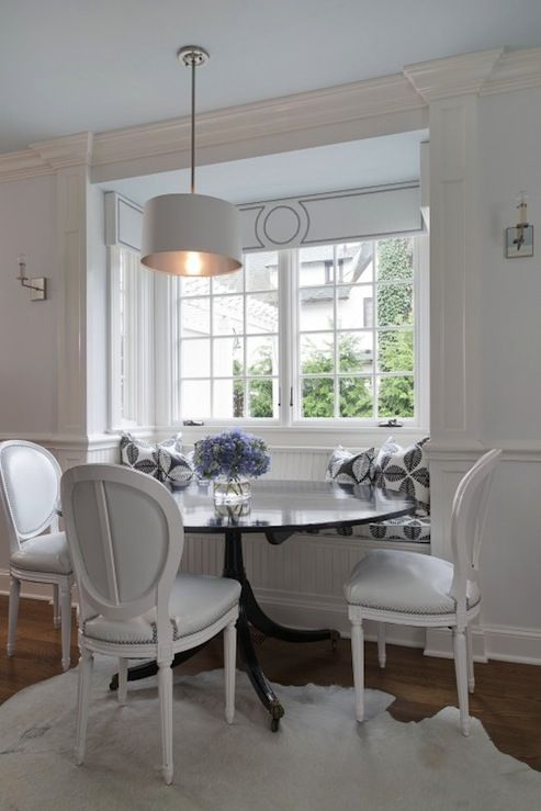 Chic monochromatic dining space with built-in beadboard banquette window seat, round black dining table, leather oval back Louis chairs, white cowhide rug, white drum pendant, white & black pillows, ceiling painted pale blue and white cornice board with nailhead trim.