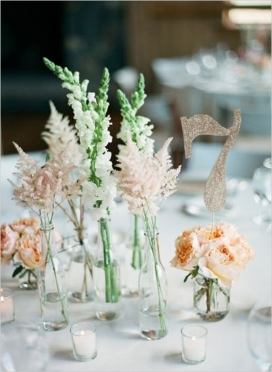 Floral and table numbers at this peach and mint wedding