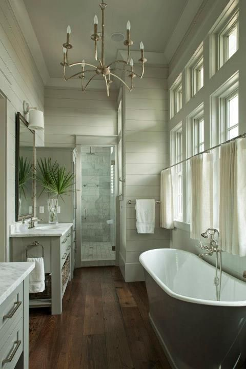 Master bathroom with gray green plank wall paneling with white crown molding & wide planked wood floors. Dreamy freestanding cast iron bath, linen cafe style drapes and 8-light metal chandelier.