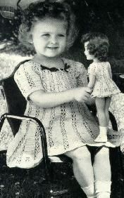 Vintage photo of little girl and her doll dressed in matching dresses circa 1940 - 1950.