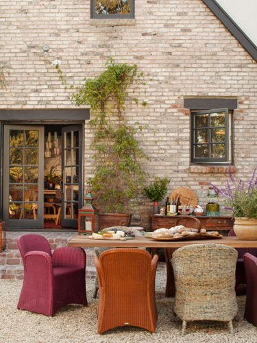Mismatched woven chairs and a teak table set the scene for meals in this outdoor entertaining area. #patio #decorating