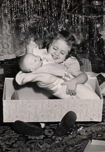 Vintage photo of little girl with her new Christmas doll, circa 1940's - 1950's.