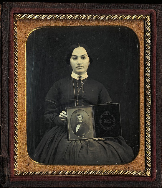 This antique photo from around 1850 instantly jumps out and grabs your attention. In it we see a young woman holding a full plate daguerreotype portrait of a man. Just who that man is (her brother, husband, even father?) remains a true mystery however. One cannot help but wonder if she sat for this image, holding her treasured photograph of a way of memorializing, for all of the time, the important bond the two had shared. #Victorian #photograph #antique #vintage #woman #family