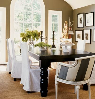 White linen slipcovers are paired with a traditional wooden table and a reupholstered garage sale chair to create a chic, modern dining space. The taupe walls add dimension and frame the rounded ceiling and windows.