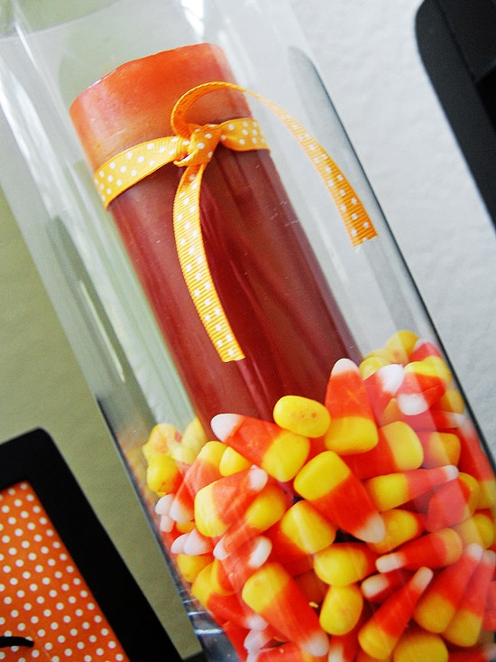 Give an orange candle Halloween flair by surrounding it with festive candy corn. Get more ideas for Halloween decor: www.bhg.com/...