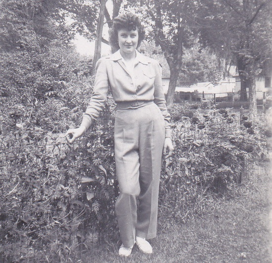 A 1940s woman wearing slacks as she poses in a backyard (I almost wonder if her outfit is actually a uniform of some kind). #vintage #1940s #fashion #trousers