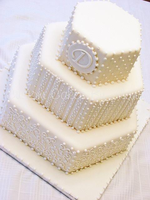 Nude, detailed, hexagon wedding cake in cream.
