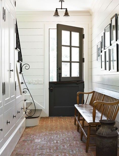 Love the combo: wood paneled walls, brick floors and dutch door - and the iron scroll on the railing.