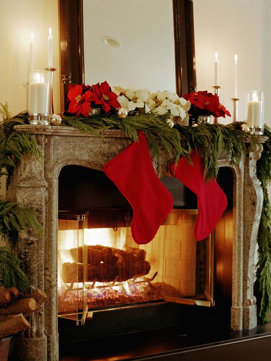 Bright red stockings with fresh greenery and poinsettias decorate the mantle. Love this look! www.hgtv.com/...