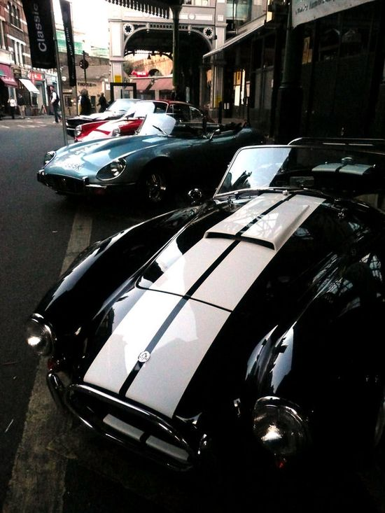 AC Cobra, Jaguar E Type, Porsche 911, average car way in the back.