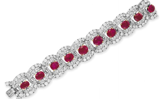 A RUBY AND DIAMOND BRACELET, BY CARTIER   Set with a graduated line of ten oval and cushion-cut rubies, each within a circular-cut diamond double oval surround, mounted in platinum and 18k gold, 6 1/8 ins., with French assay marks  Signed Cartier, Paris, no. 07302. Elizabeth Taylor collection.