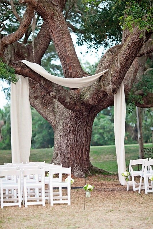Fabric draped over a tree to frame the wedding ceremony, mason jars filled with flowers on Sheppard hooks lined the aisle