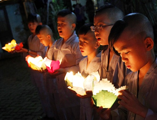 Buddhist novice monks hold candles at a ceremony at the Duoc Thuong pagoda in Hanoi, Vietnam.