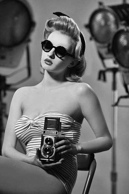 1950s hair, sunglasses, swimsuit, and camera. Amazing.