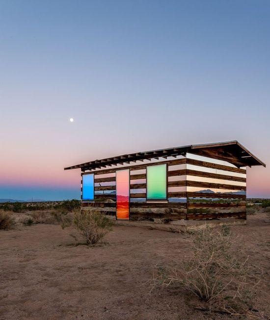 """Phillip K. Smith III est un artiste américain, sa dernière installation baptisée """"Lucid Stead"""" est située au milieu du High Desert. Cette installation artistique est basée sur un cabanon abandonné vieux de 70 ans. Durant la journée, l'oeuvre reflète son environnement à l'aide de miroirs placés dans les ouvertures et au coucher du soleil, la lumière commence progressivement à envahir la cabane où les ouvertures se transforment en blocs colorés."""