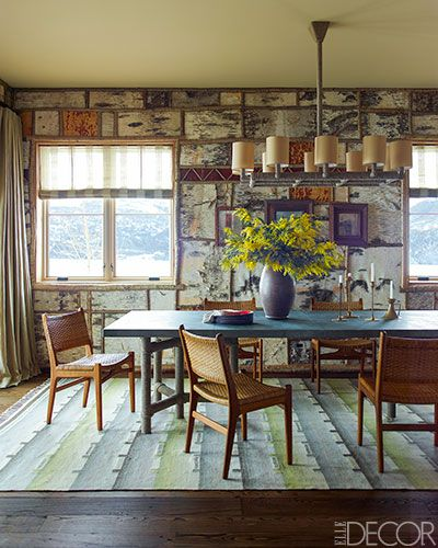 The walls in dining room are lined in a grid of birch veneer framed with split branches.