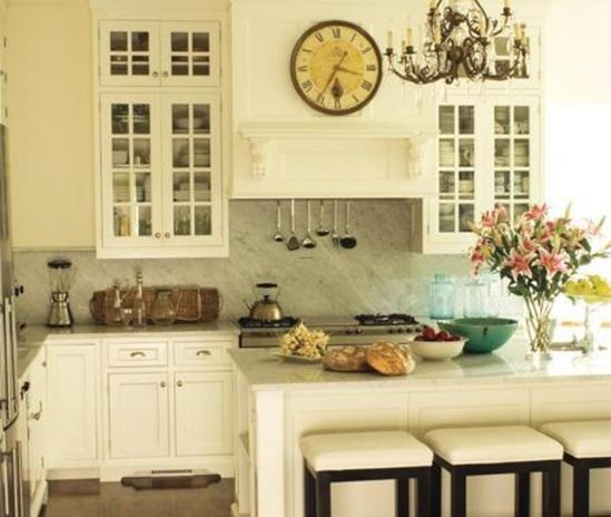 The clock, chandelier, shelf and open cabinets give this kitchen a French Country look.