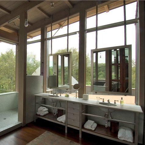 This bathroom by Mell Lawrence Architects is surrounded by windows on three sides and opens to a sun porch, creating an indoor/outdoor flow. Photo by Hester + Hardaway.