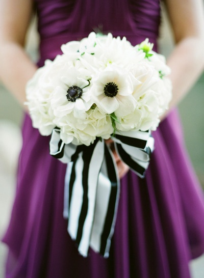 white bouquet tied up with black and white striped ribbon