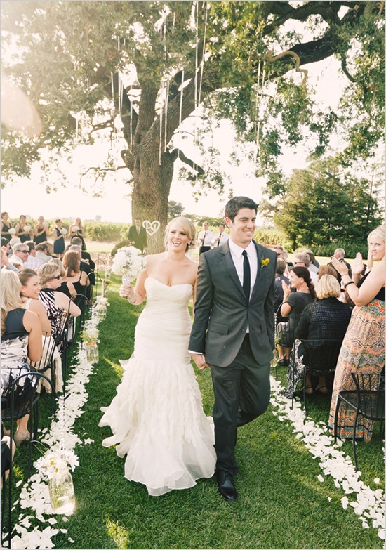 wedding under tree and flowers lining the aisle