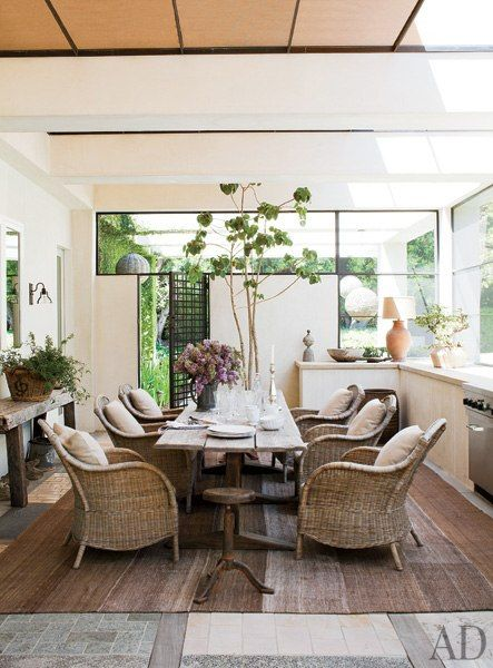 30 Amazing Celebrity Dining Rooms via AD  - The screened porch of Portia de Rossi and Ellen DeGeneres's Beverly Hills estate includes a 19th-century trestle table and wicker armchairs for informal dining.