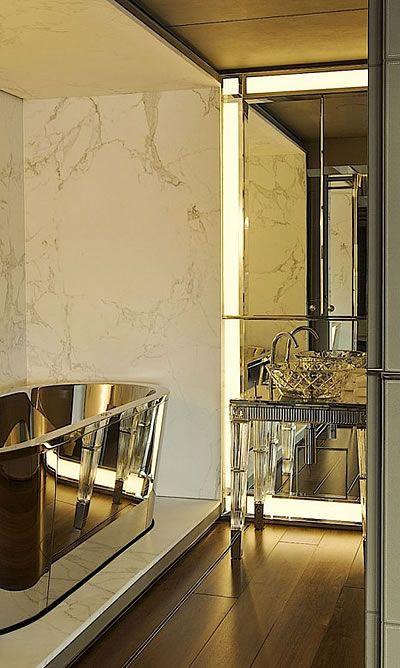 złota wolnostojąca wanna w luksusowym wnętrzu z kryształowymi umywalkami