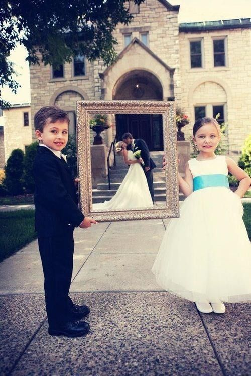 Ring bearer & flower girl holding picture frame with bride & groom posing behind it!