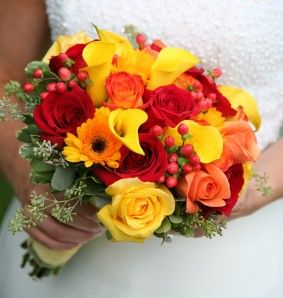 A fresh hand-tied bouquet of yellow calla lilies, peach, yellow and red roses, yellow gerberas and eucalyptus seeds.