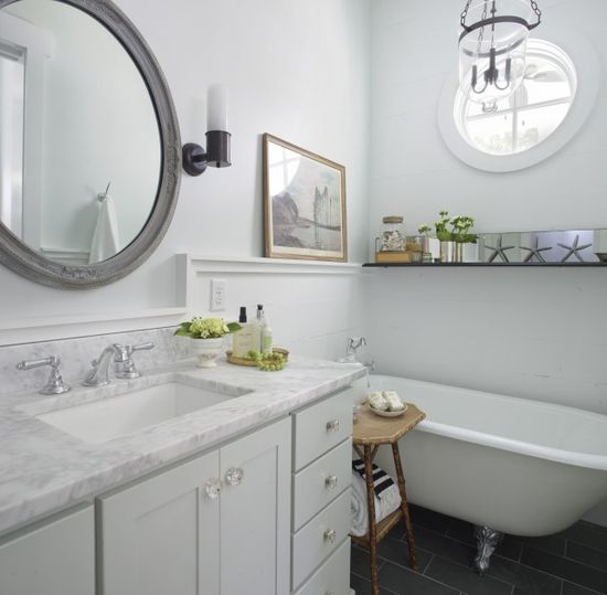 trim.  bathrooms - gray vintage antique round mirror pale gray walls clawfoot tub charcoal gray slate tiles floor pale gray single bathroom vanity cabinet calcutta marble countertop glass knobs