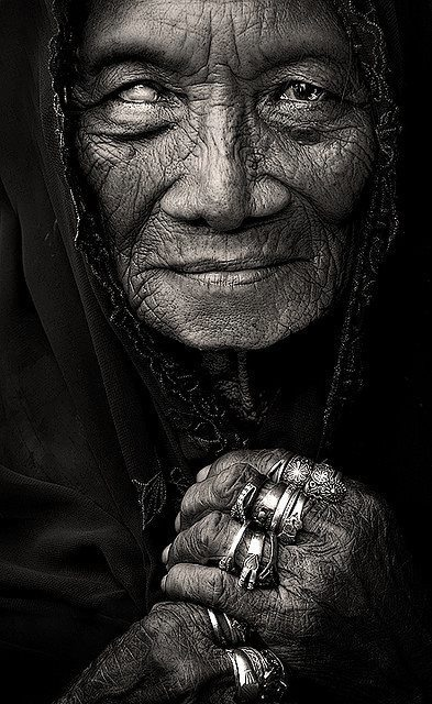 i love the clarity of this low key image. the depth and texture you can see in the woman's face. the lines created by the rings on her fingers that lead directly to the lines of her hood. so much emotion.