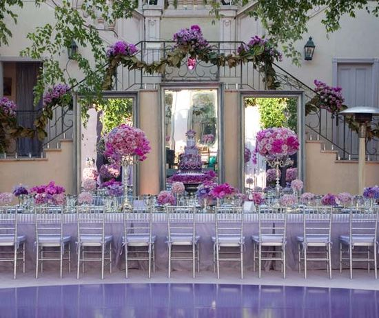 Tall centerpieces and a garland-adorned staircase frame the dramatic purple cake.