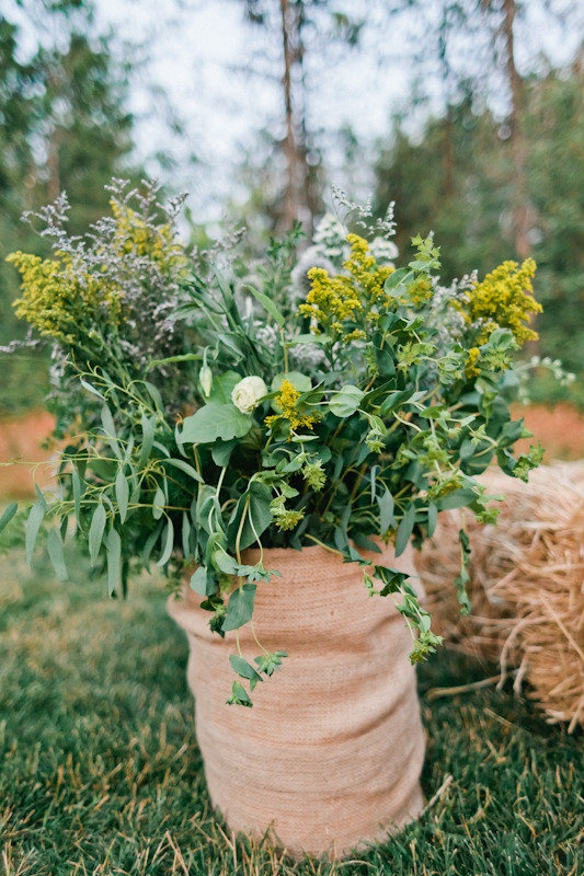 This is kind of cool for rustic or outdoor weddings. Wrap big buckets of plants in burlap. Easy and looks great! Photography by aliciabrownphotog..., Wedding Coordination by glacierparkweddin..., Floral Design by mumsflowers.net