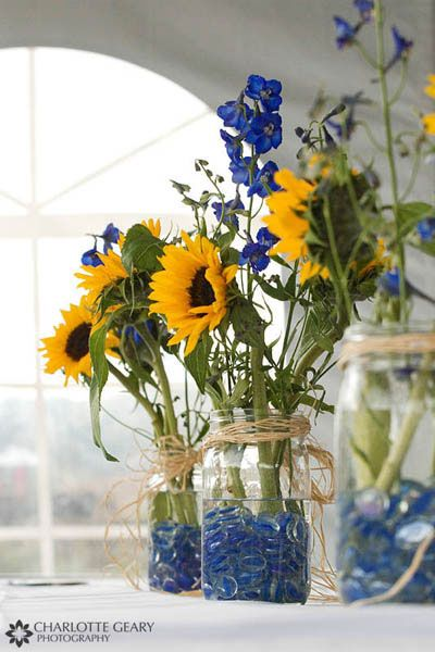 Sunflower table arrangements--love the use of mason jars, sticks to the yellow/purple color theme. I'd put more flowers in each jar, though, and keep them a little shorter.