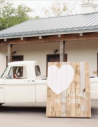 large wooden wedding sign leaning antique-y truck.